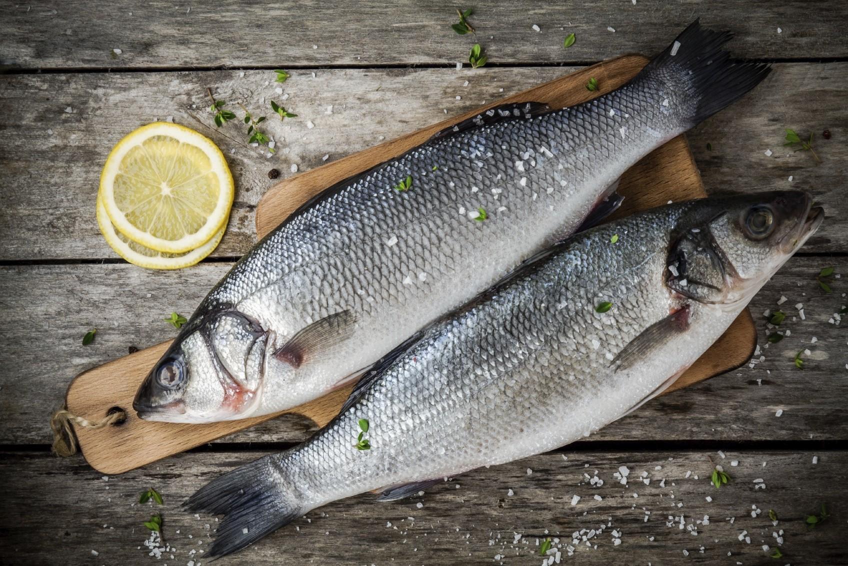 two raw fresh sea bass on a cutting board with lemon and sea salt on wooden rustic table